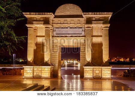 Arch of the Puerta del Puente on the north side of the Roman bridge in the night illumination. Cordoba. Andalusia.