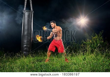 Young athletic male fighter working out with a punching bag outdoors at night with fire burning on his boxing gloves copyspace power strength masculinity fierce fiery flames hot sexy sportsman focused.