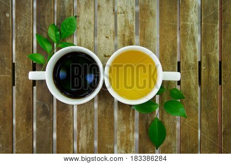Cup of black coffee cup of jasmine tea with couple of green leaf on wooden table. Top view.