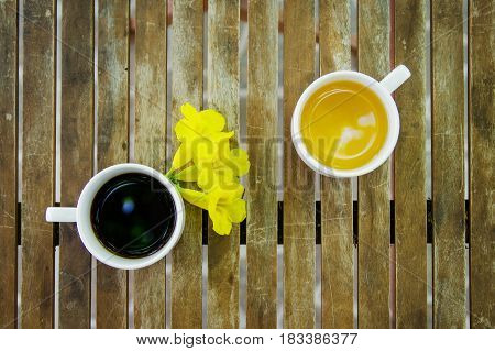 Cup of black coffeeCup of jasmine tea with yellow flowers on wooden table. Top view.