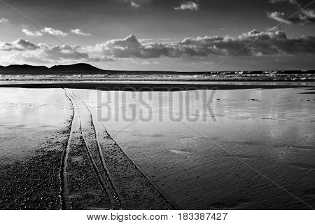 a view of the Famara Beach in Lanzarote, Canary Islands, Spain, with La Graciosa island in the background, in black and white