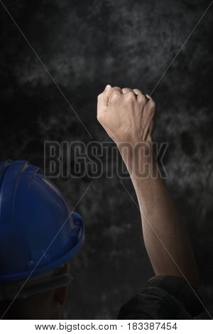 closeup of a young caucasian man seen from behind wearing a blue hard hat and with his fist raised to the air, against a gradient gray background