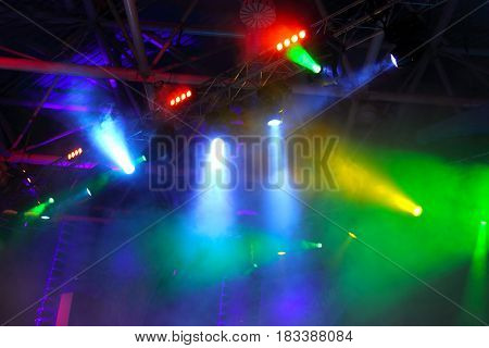 lighting equipment  at concert - colored spotlights on ceiling in smoke