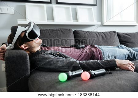 Image of young happy man lies on sofa at home indoors wearing 3d virtual reality glasses.