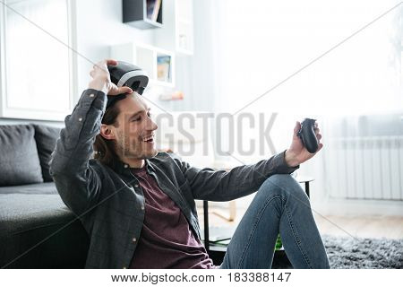 Image of young smiling man sitting at home indoors play games with 3d virtual reality glasses. Looking aside.