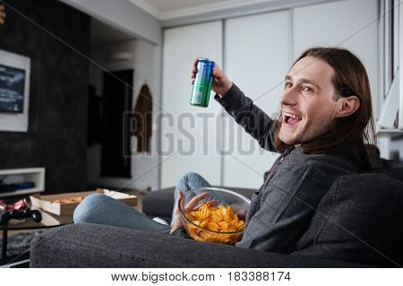 Image of young man sitting at home indoors eating crisps. Looking aside while watch TV.