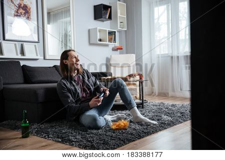 Picture of young happy man sitting at home indoors play games with joystick near crisps. Looking aside.