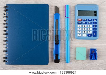 Notepad, Calculator And Other Stationery Tools On Wooden Table