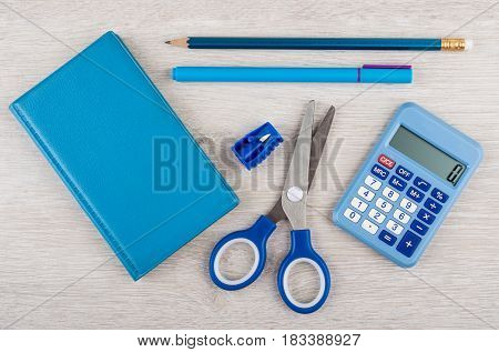 Blue Notepad, Scissors, Calculator And Other Tools On Wooden Table