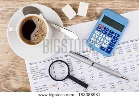 Financial Printout, Calculator, Pen, Magnifying Glass And Coffee On Table