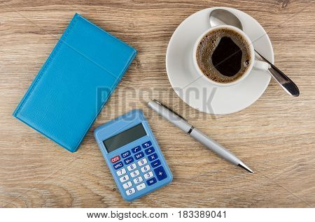 Blue Notepad, Calculator, Ballpoint Pen And Coffee On Table