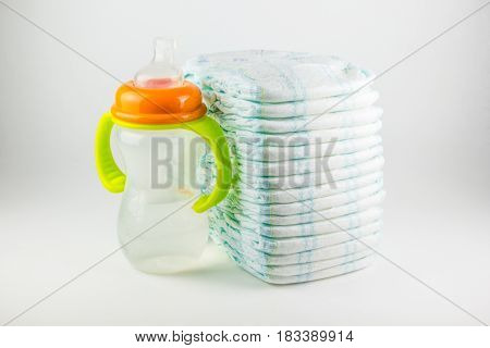Baby diapers and bottle on a white background