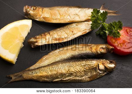 golden brown smoked sprats with slice tomato parsley and lemon on slate