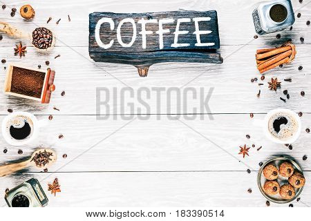 Background of light textured wooden boards with coffee beans, ground coffee, cups of black coffee and spices. Wood signboard with text 'Coffee'