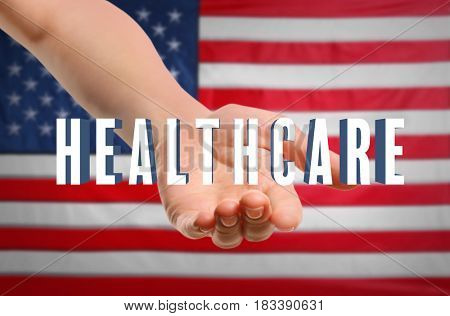 Word HEALTHCARE and female hand on USA flag background