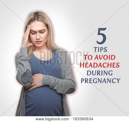 Health care concept. Pregnant woman suffering from headache on light background