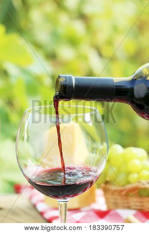 Pouring red wine into the glass, close up
