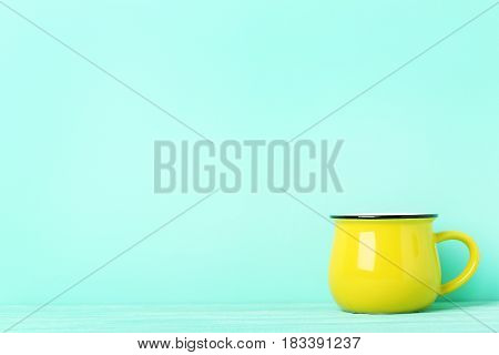 Yellow mug on a green background, close up
