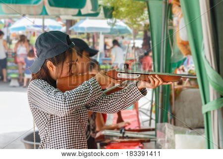 Thai girl playing shooting games in temple fair Thailand