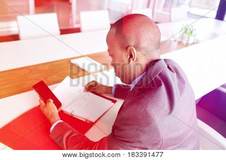 High angle view of young businessman with file using mobile phone at conference table