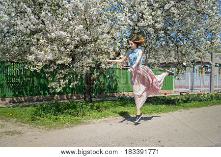 A young girl runs bouncing against the background of a blossoming cherry tree