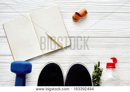 Fitness Concept With Dumbbells And Sneakers And Water Bottle Notebook Pencil Centimeter Tape On Whit