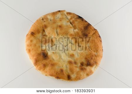 piece of khachapuri with meat lying on a white table