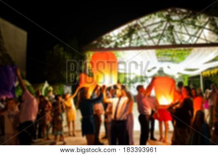 Blur Photo Of Crowd People With Sky Lantern At Wedding Outdoor At Night.