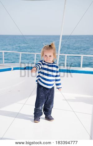 traveling vacation. small baby boy sailor or cute child captain of yacht boat or ship white color with blonde hair in stripped marine shirt outdoor on natural background with blue sea or ocean water