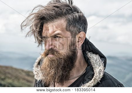 hipster bearded man long beard brutal caucasian with moustache unshaven guy with stylish hair getting beards haircut on windy mountain top on natural cloudy sky