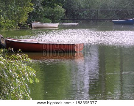 romantic red rowboat on the green water
