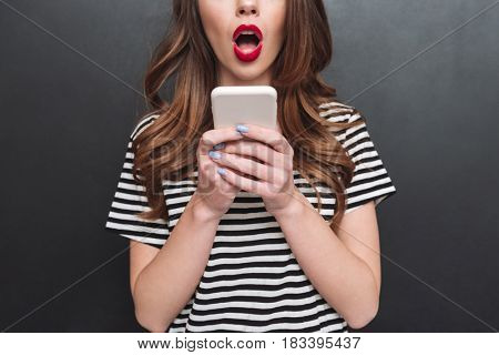 Close up of young beautiful woman hollding phone isolated over grey background