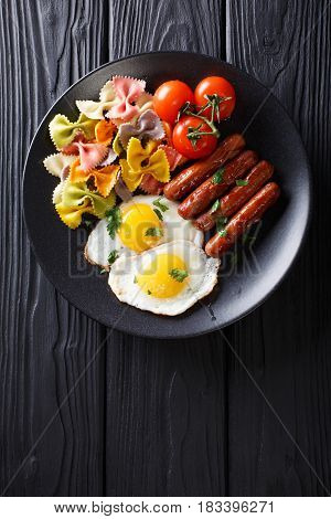 Hearty Breakfast: Fried Eggs, Sausages, Farfalle Pasta And Tomatoes Close-up. Vertical Top View