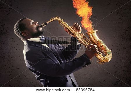 African-American musician playing saxophone and fire coming out of instrument on dark background