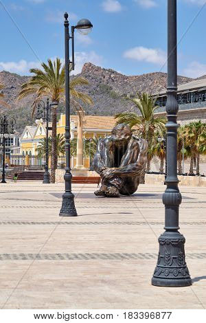 The huge iron man. Cartagena, Spain - July 13, 2016: Monument El Zulo, created by sculptor Victor Ochoa. Dedicated to the victims of terror in Madrid in 2004