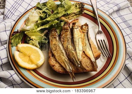 golden brown smoked sprats with bread salad and slice lemon a plate