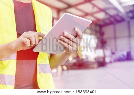 Midsection of manual worker using digital tablet in metal industry