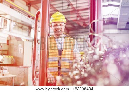 Portrait of manual worker pulling hand truck with steel shavings in factory