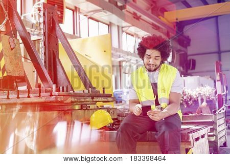 Young manual worker using mobile phone in metal industry
