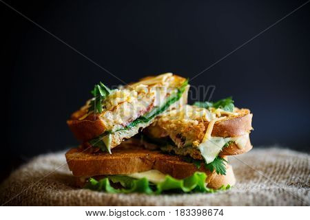 Fried hot sandwich with sausage and salad leaves on a black background