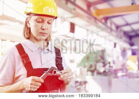 Mature female worker measuring metal with caliper in industry
