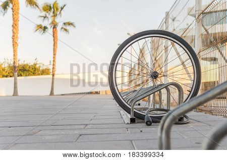 Stolen bicycle, Chained front bicycle wheel locked. A damaged bike wheel is all that is left, a single bicycle wheel on the street due to stealing.
