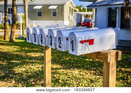 Pine Island, FL, USA - 02/14/2017: Line of Mail boxes numbered one to six on a wooden post at Pine Island FL