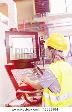 Female worker operating machinery at control panel in factory