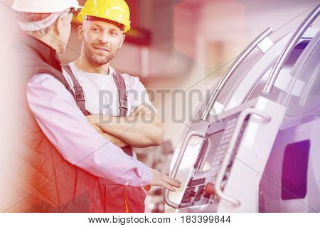 Mid adult manual worker having discussion with colleague by machinery in industry