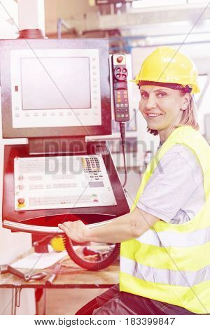 Portrait of female worker operating machinery at control panel in factory