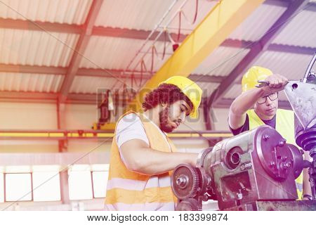 Low angle view of manual workers working on machinery in metal industry