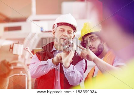 Supervisor and manual worker discussing over metal in industry