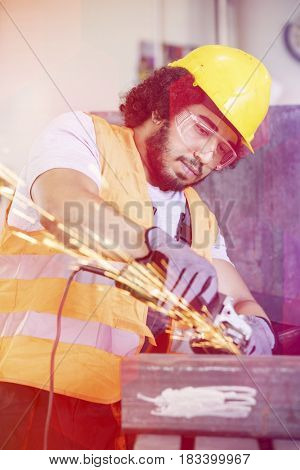 Young manual worker in protective workwear grinding metal in industry