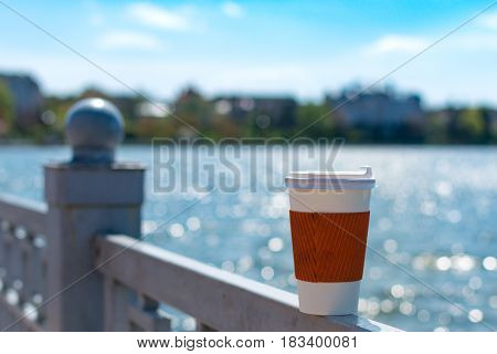 Coffee single cup on the fence The lake and the city in bokeh
